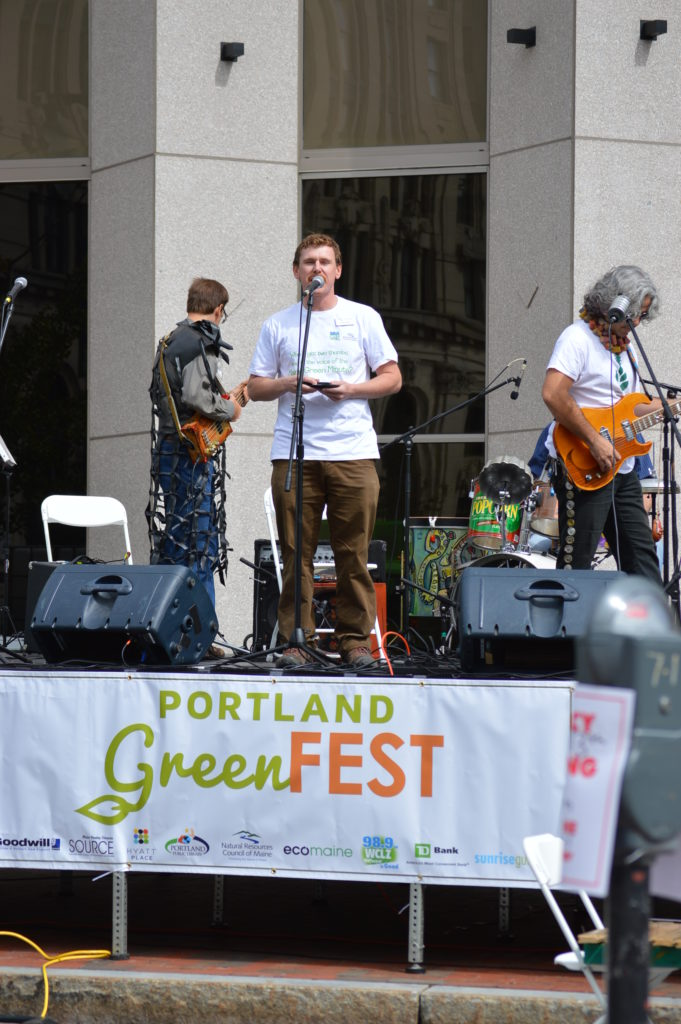 NRCM's Todd Martin reads some Maine Green Minutes on the stage at Greenfest
