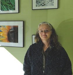 Terry Sprague of North Haven in front of her photography exhibit at NRCM's office in Augusta.