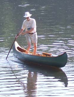 Sam H. of Skowhegan takes a break from paddling to pole his canoe down the river.