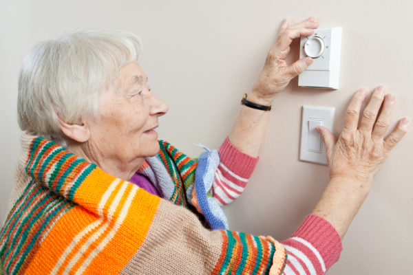 elderly woman with thermostat