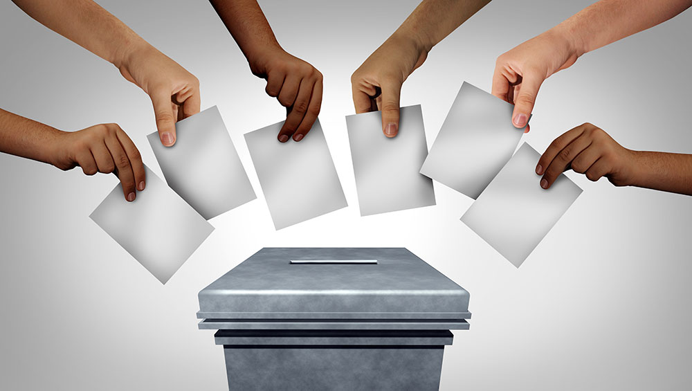 Hands voting with ballot box
