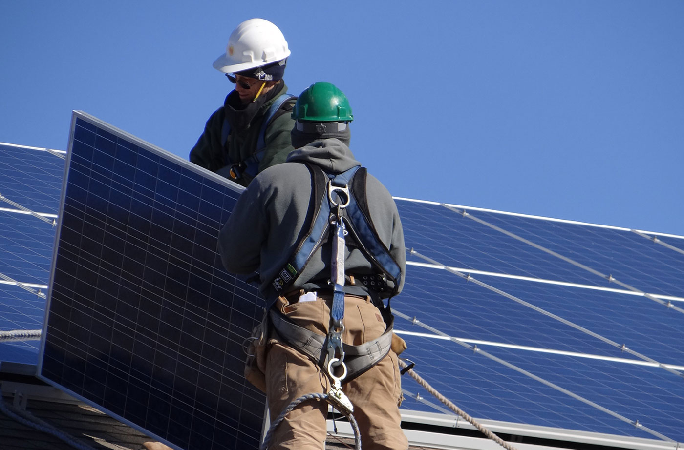 solar workers install panels on roof in Maine