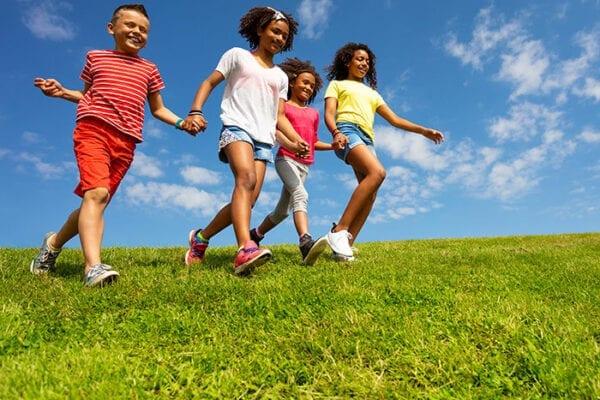 children holding hands running through grass