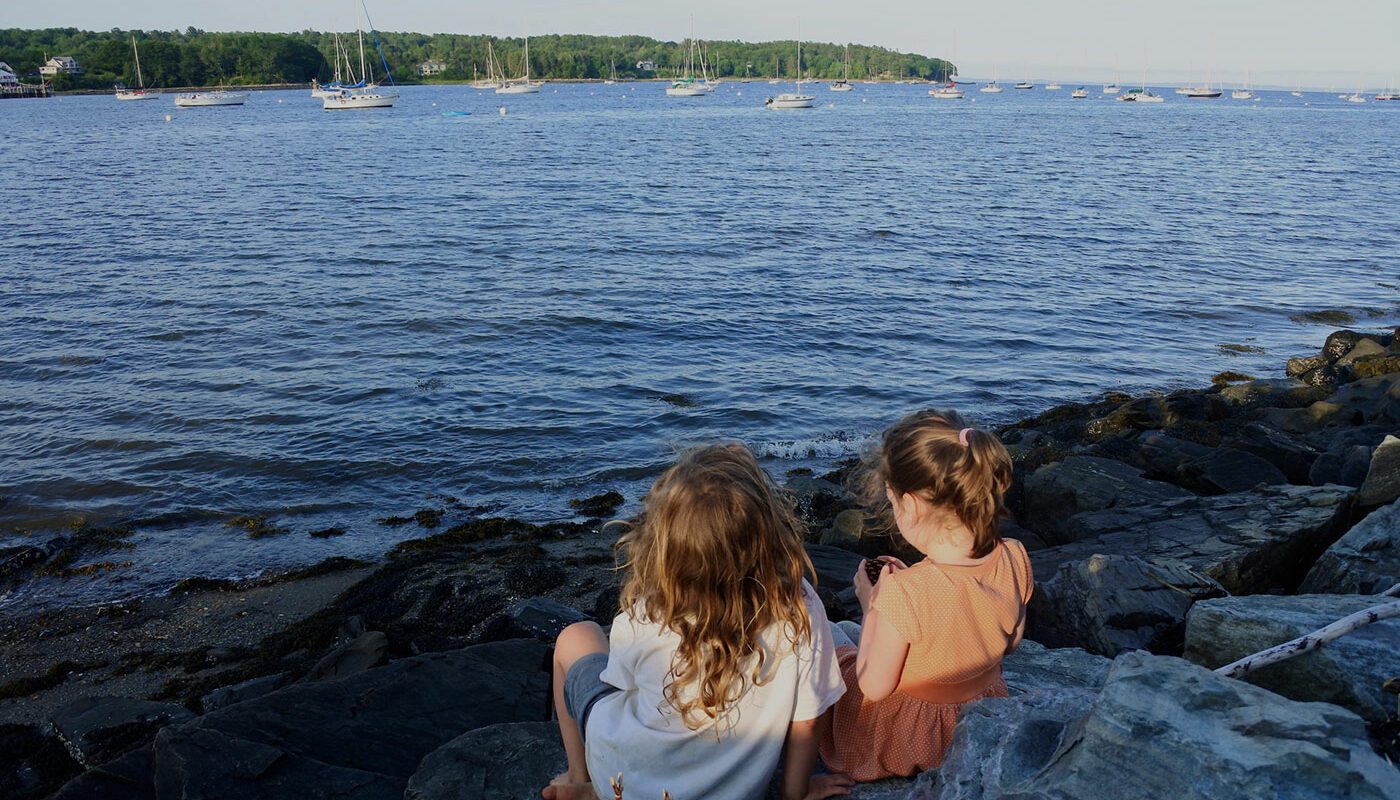 two girls sitting by shore