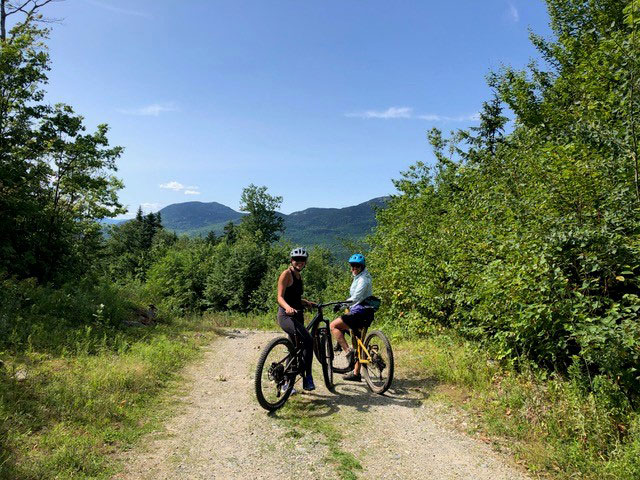 two smiling mountain bikers on trail