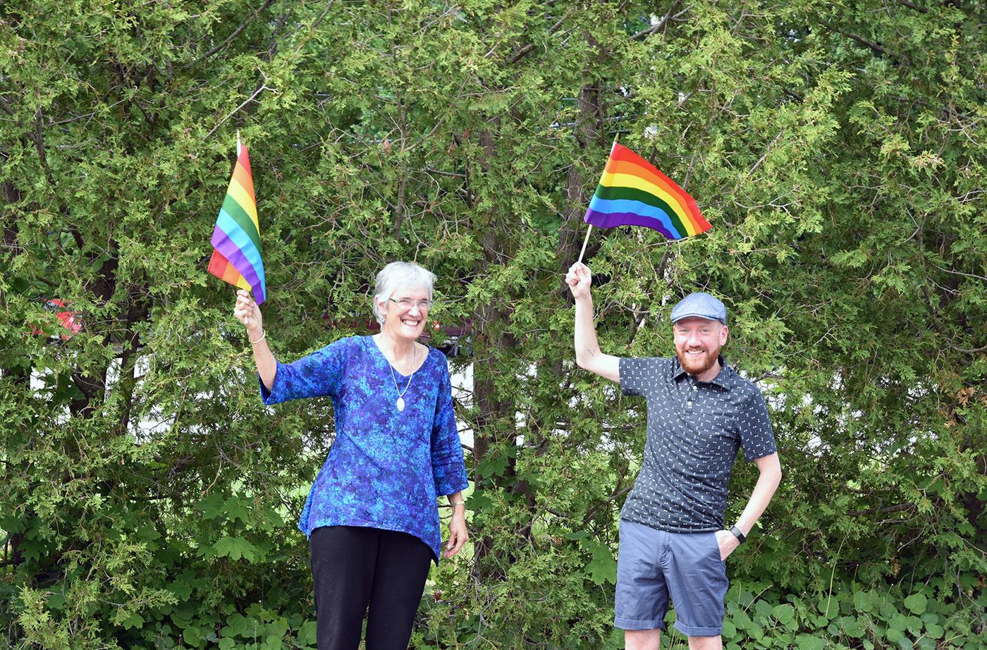 Lisa and Levi waving pride flags