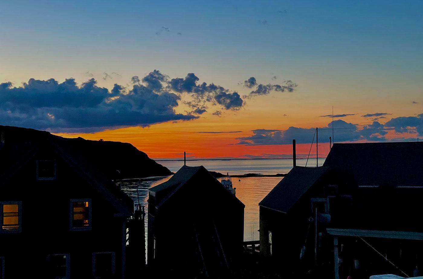 Sunrise over buildings at Maine coast